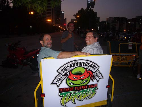 Pete Maresca and Harold Sipe hitch a ride on a TMNT-themed pedicab